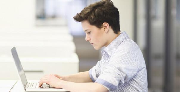 Подросток сидит за ноутбуком